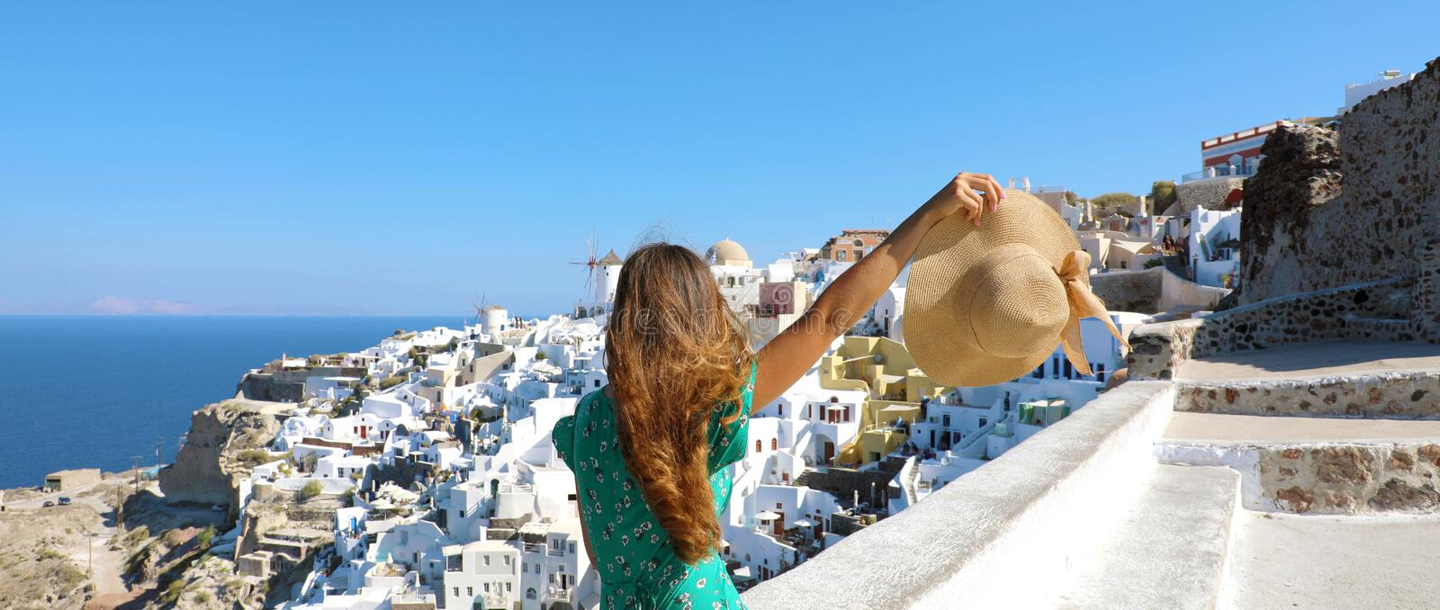 Traveler girl enjoying Santorini view with open arm and hat in the hand. Banner panorama royalty free stock photo