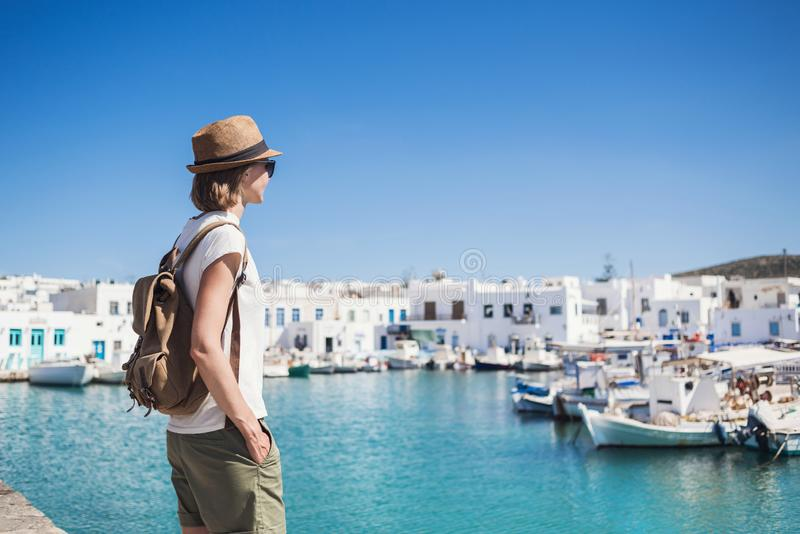 Traveler girl enjoying vacation in Greece. Young woman wearing hat looking at greek village with sea. Summer holidays, vacations, stock photo