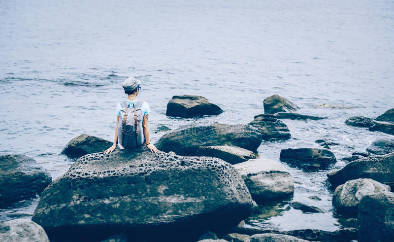 Traveler girl sitting on stone in the sea stock image