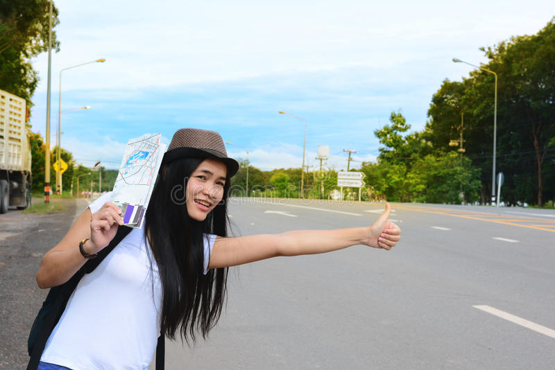 A traveler girl in white shirt hold a map and waving her hand stock photography