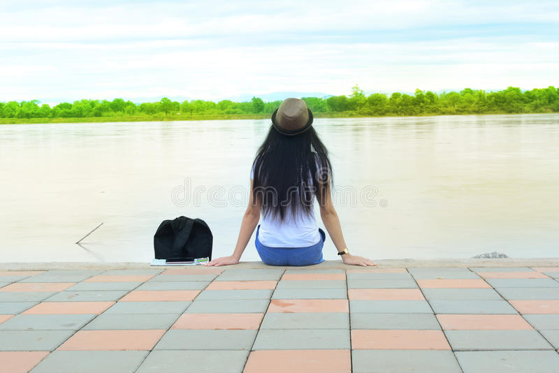 A traveler girl in white shirt sitting at the cement ground stock photo