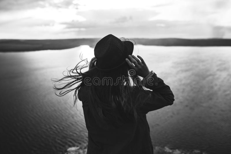 Traveler girl with windy hair holding hat and looking at evening sky on top of rock mountain.Loneliness and melancholy concept. stock photos