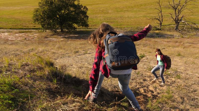 Traveler girls descend from the mountain. Hiker Girl. Family of tourists traveling at sunset. sisters with backpacks royalty free stock photography