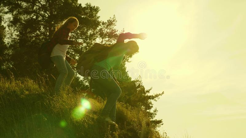 Traveler girls descend from the mountain. Hiker Girl. Family of tourists traveling at sunset. sisters with backpacks stock photos