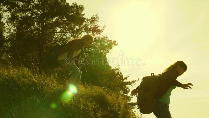 Traveler girls descend from the mountain. Hiker Girl. Family of tourists traveling at sunset. sisters with backpacks stock photography