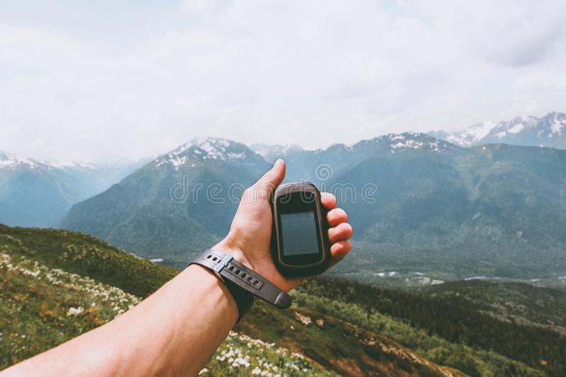 Traveler hand holding gps navigator tracker looking for location coordinates. Hiking in mountains Travel Lifestyle concept survival adventure summer vacations stock photo