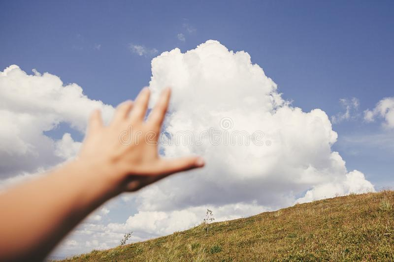 Traveler hand reaching out to mountains and sky clouds. focus on royalty free stock images
