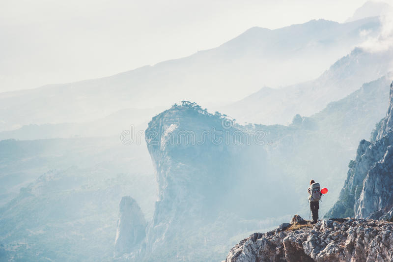 Traveler hiker on cliff traveling with backpack stock photo