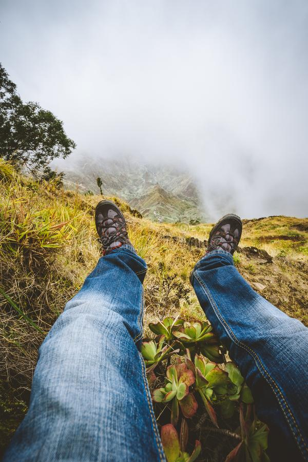 Traveler hiking boots over impressive verdant Xo-Xo valley with mountain peaks, rugged cliffs in fog on Santo Antao. Traveler hiking boots over impressive royalty free stock photos