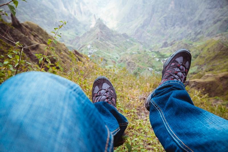 Traveler hiking boots over impressive verdant Xo-Xo valley with mountain peaks, rugged cliffs on Santo Antao Island. Cape Verde stock photography