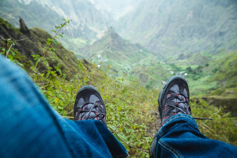 Traveler hiking boots over impressive verdant Xo-Xo valley with mountain peaks, rugged cliffs on Santo Antao Island. Cape Verde stock images