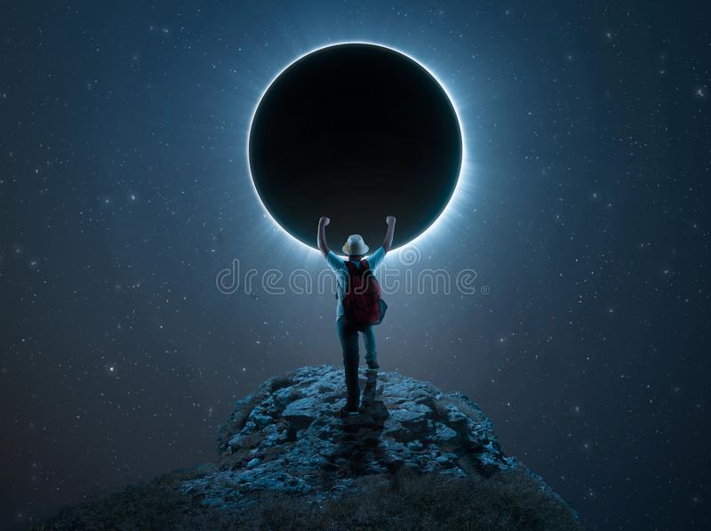 Discover the eclipse. Traveler kid rising his hands on a peak in front of eclipse stock images