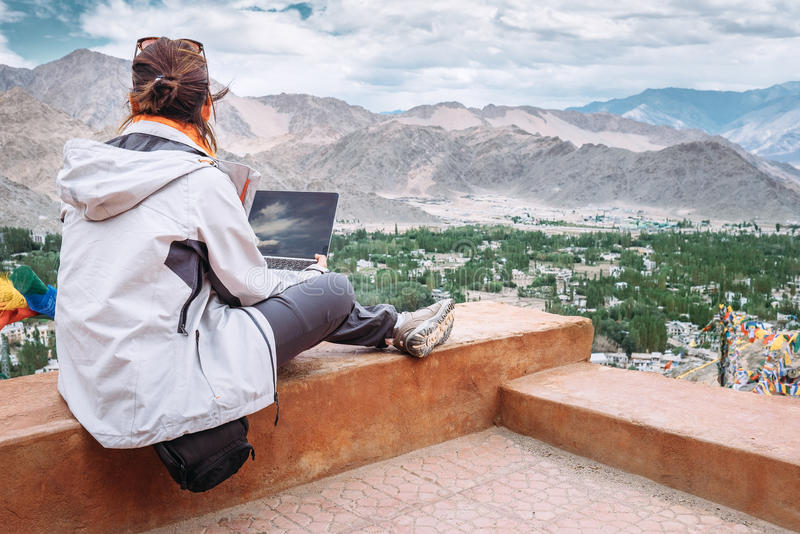 Traveler with laptop sits on top view point on the mountain valley stock images