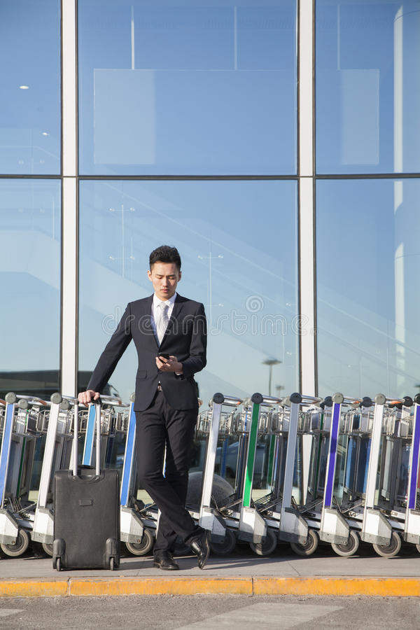 Download Traveler Looking At Cellphone Next To Row Of Luggage Carts Stock Image - Image: 31132253