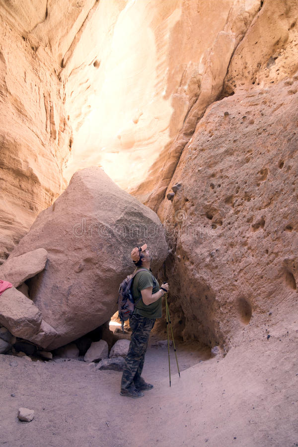 The traveler looks up in the narrow canyon. Kasha-Katuwe Tent Rocks National Monument, Cochiti, NM, USA royalty free stock photography