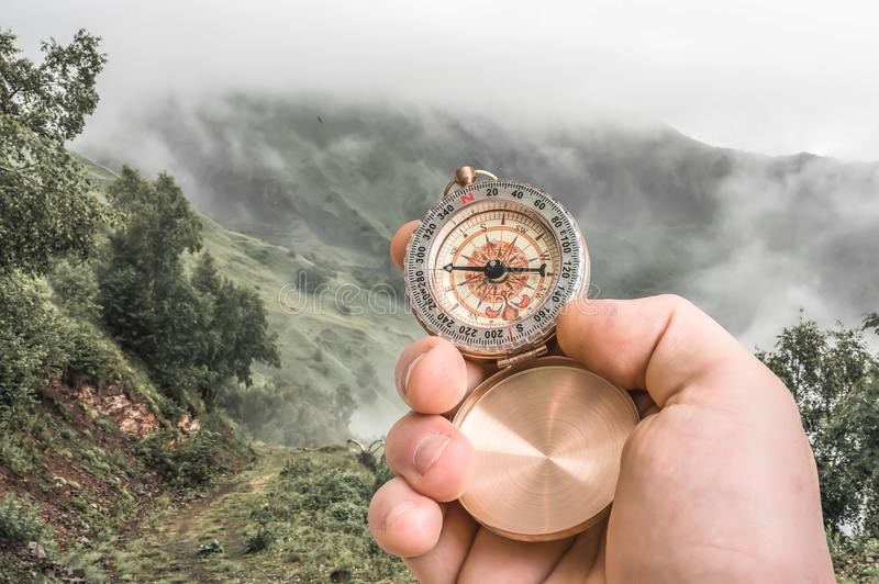 Traveler man with compass seeking a right way through the fog. In mountains - navigation concept royalty free stock photography