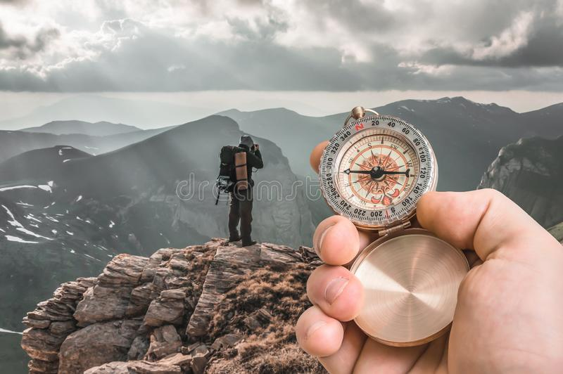 Traveler man with compass seeking a right way in the mountains. Navigation concept stock photo