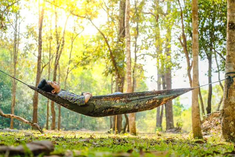 Traveler man hiking and relaxing in hammock autumn woods royalty free stock photos