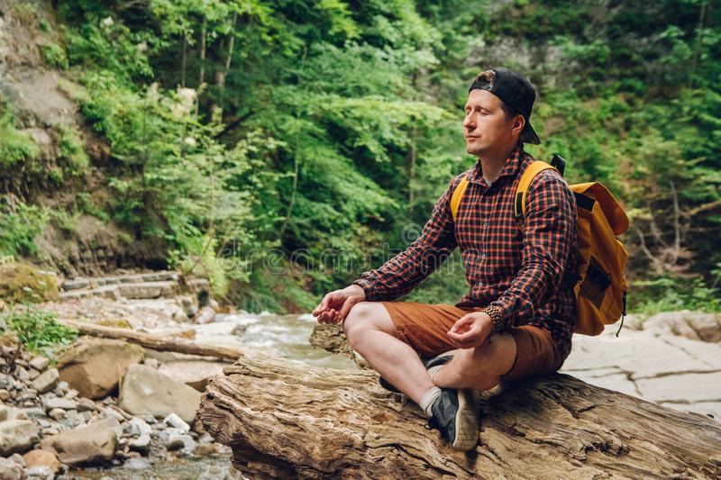 Traveler man in a meditative position with a backpack sitting on a tree trunk against the background of the forest and royalty free stock images