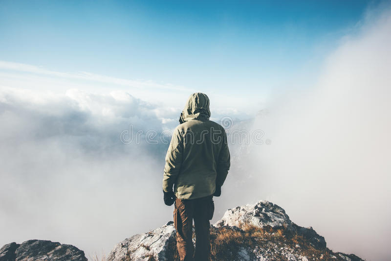Traveler Man on mountain summit alone. Enjoying aerial view over clouds Travel Lifestyle success concept adventure active vacations outdoor rear view royalty free stock photography