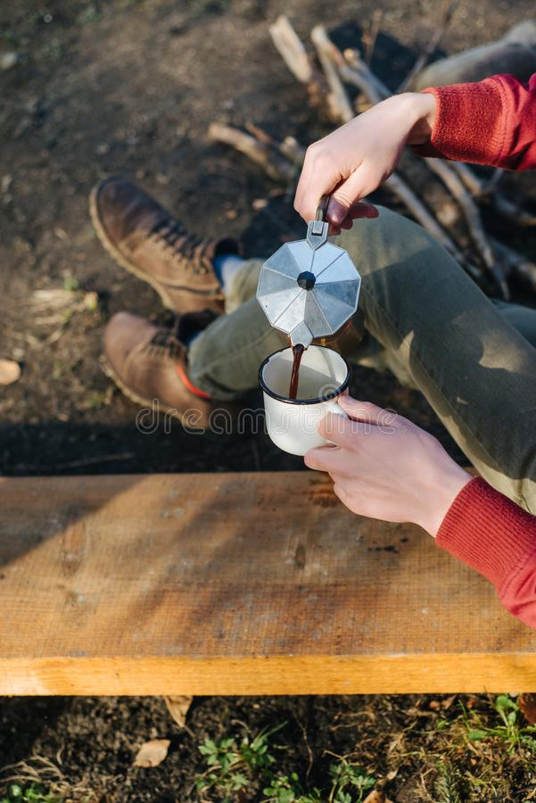 Traveler man in red jacket pours itself hot beverage in mountains near to bonfire, relaxing after trekking. Young male sitting and holding a mug of coffee royalty free stock photos