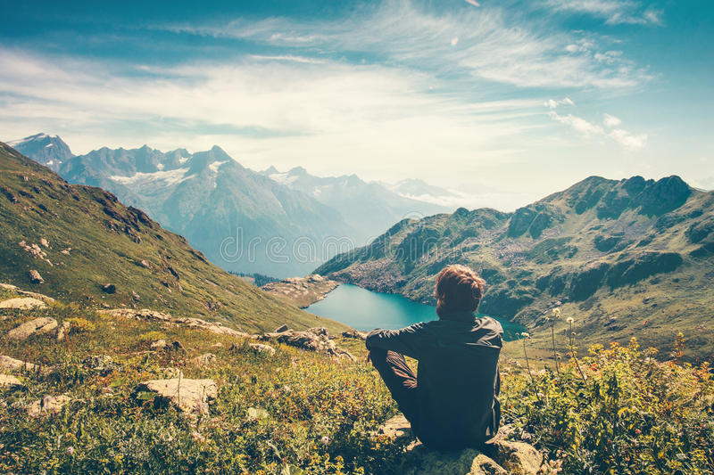 Traveler Man relaxing meditation with serene view. Mountains and lake landscape Travel Lifestyle hiking concept summer vacations outdoor stock photography