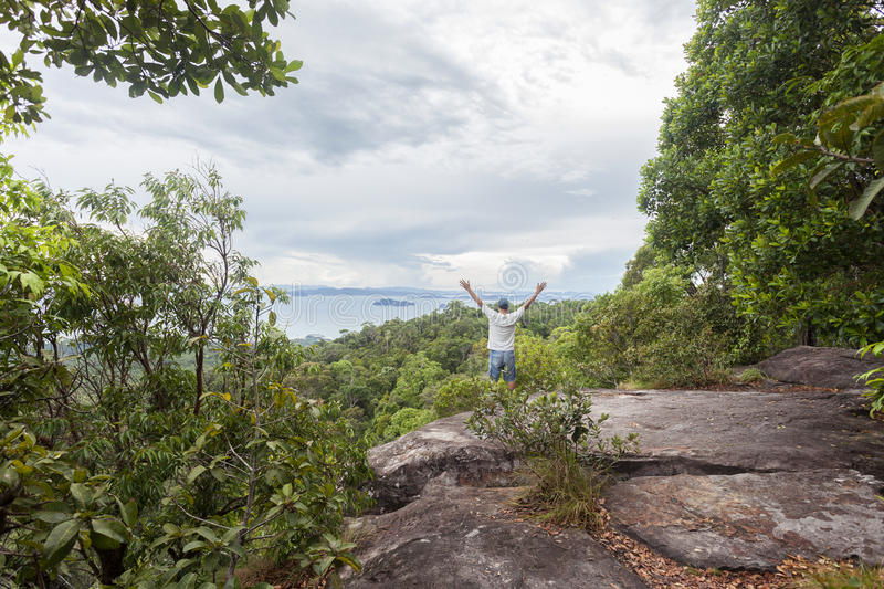 Traveler man standing on big stone holding his hand up and see l royalty free stock photography