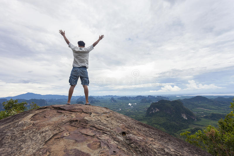 Traveler man standing on big stone holding his hand up and see l stock photography
