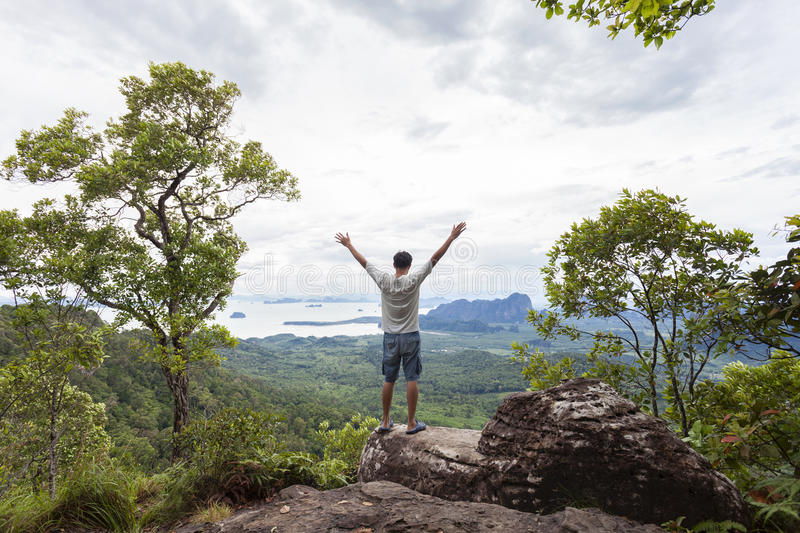 Traveler man standing on big stone holding his hand up and see l stock image