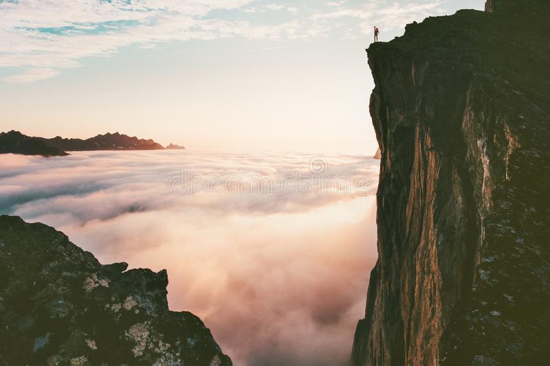 Traveler man standing on the edge cliff over clouds. Sunset mountains travel adventure lifestyle journey vacations in Norway royalty free stock image