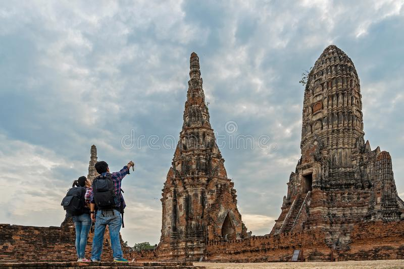 Traveler man and women with backpack walking in asia temple Ayuttaya, tourists travel in Thailand. Traveler men and women with backpack walking in asia temple royalty free stock photography