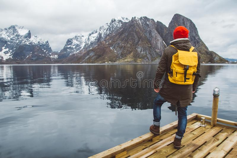 Traveler man with a yellow backpack wearing a red hat standing on the background of mountain and lake wooden pier stock image