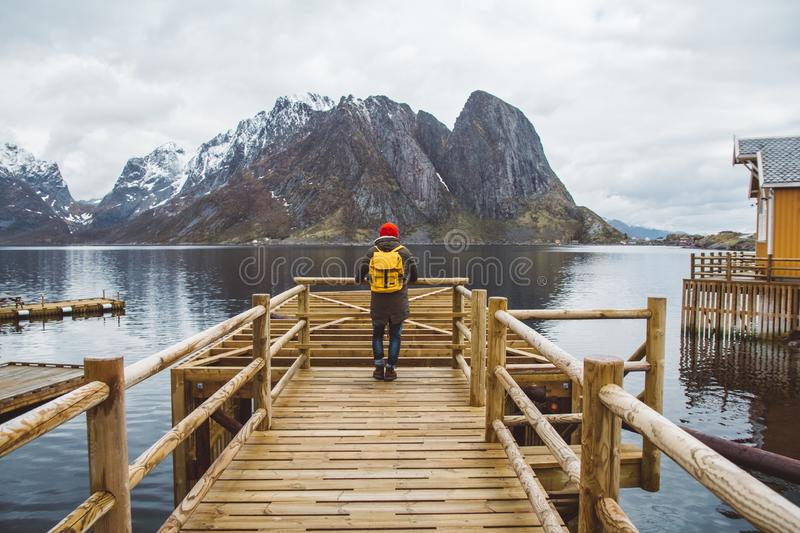 Traveler man with a yellow backpack wearing a red hat standing on the background of mountain and lake wooden pier stock photography