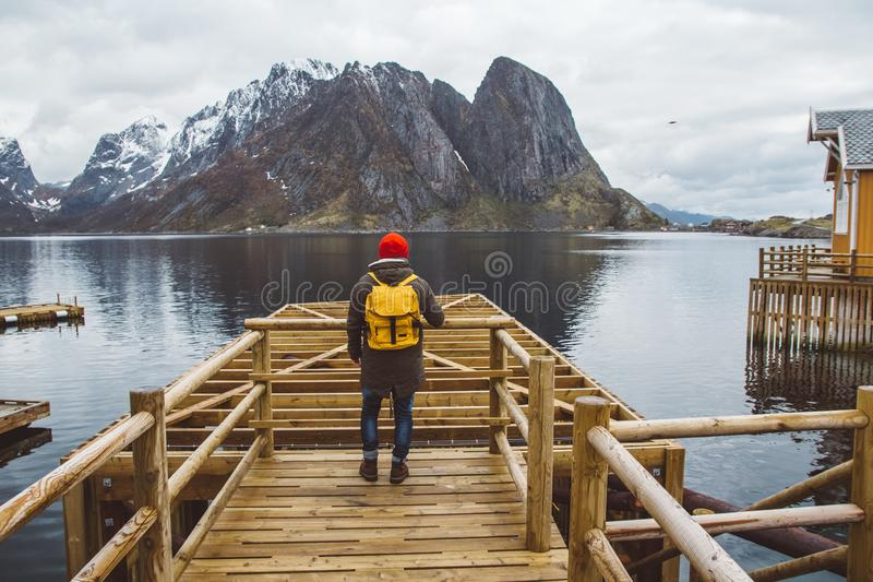 Traveler man with a yellow backpack wearing a red hat standing on the background of mountain and lake wooden pier stock photos