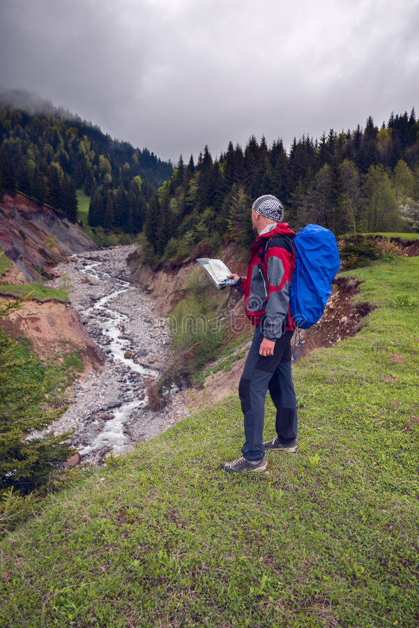 Traveler with map on shore of a mountain river. In his hands is standing on the shore of a mountain river and looking on the heavy clouds on the horizon - search royalty free stock photography