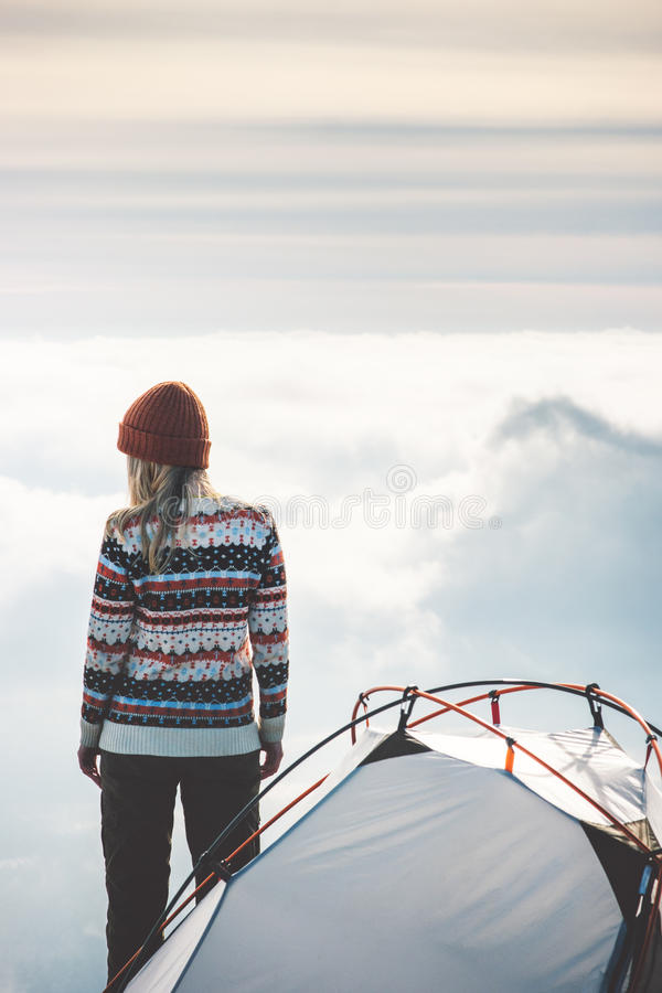 Traveler on mountain summit and tent camping. Foggy clouds landscape on background Travel Lifestyle concept adventure vacations outdoor stock photo