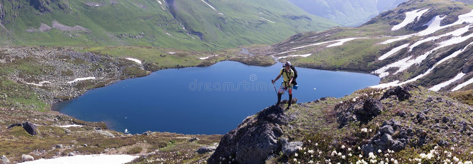 Traveling man on a background of alpine meadows with a lake. stock photo