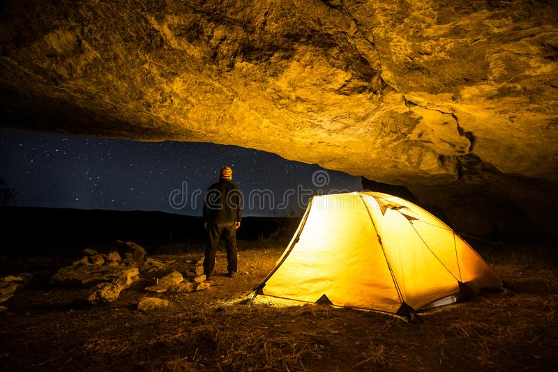 Traveler near the glowing camping tent in the night grotto under a starry sky stock images