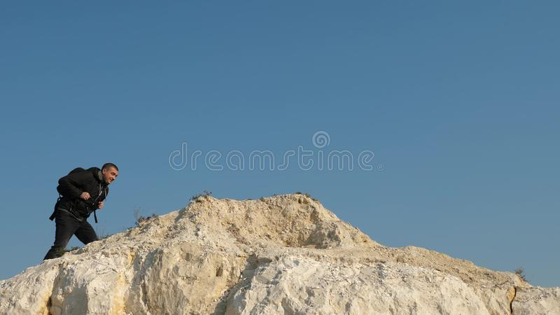 Traveler overcomes a mountain pass. three climbers climb one after the other on a white rock. teamwork of business. Traveler overcomes a mountain pass. three stock image