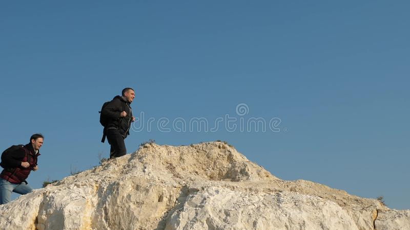 Traveler overcomes a mountain pass. three climbers climb one after the other on a white rock. teamwork of business. Traveler overcomes a mountain pass. three royalty free stock images