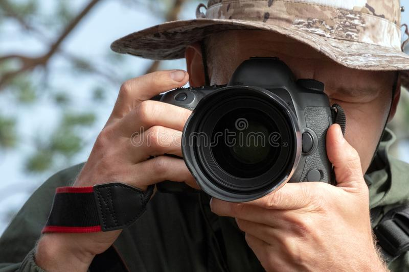 Traveler photographer in a hat looks into the camera lens. Lifestyle, photo story, natural photography. Travel and royalty free stock photo