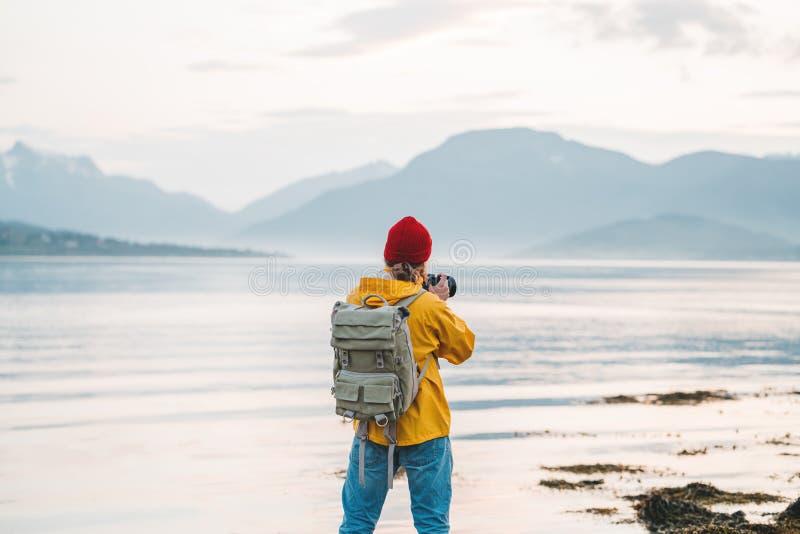 Traveler photographer wearing yellow raincoat taking photo by professional camera of fantastic scandinavia nature stock photography