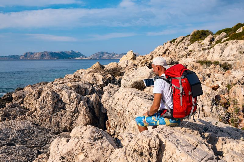 Traveler with a portable solar battery attached to his backpack stock photos