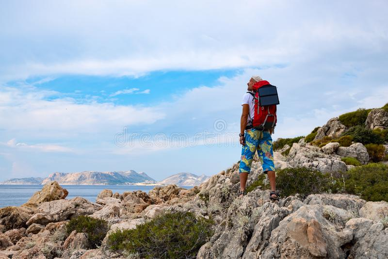 Traveler with a portable solar battery attached to his backpack royalty free stock images