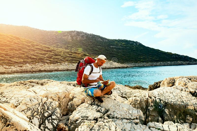 Traveler with a portable solar battery attached to his backpack stock image