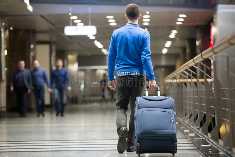 Traveler pulling suitcase at airport stock photos
