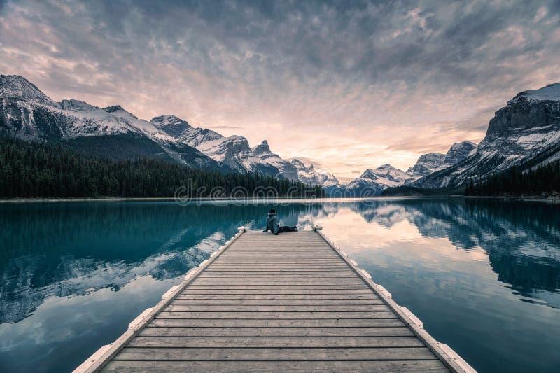 Traveler relaxing on wooden pier in Maligne lake at Spirit island, Jasper national park stock photo