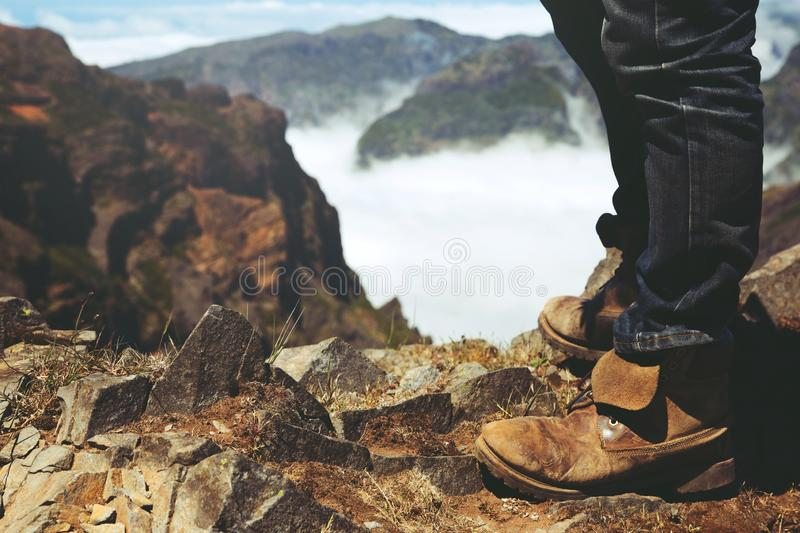 Traveler resting man hipster hiking boots Standing on a high mountain peak. Having enjoying wonderful breathtaking the forest mountain rocks view. Freedom stock photo
