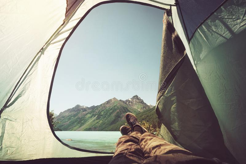The traveler`s legs in hiking boots in an outdoor tent.bonfire on the river bank. concept of outdoor activities stock photos