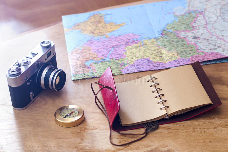 Traveler`s things: old camera, map, notebook, compass on a wooden background royalty free stock image